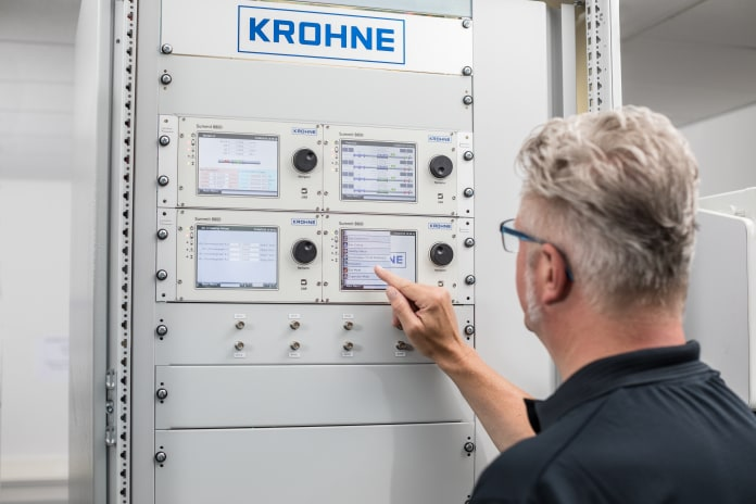 Техник настраивает вычислитель расхода SUMMIT 8800, установленный в шкафу управления